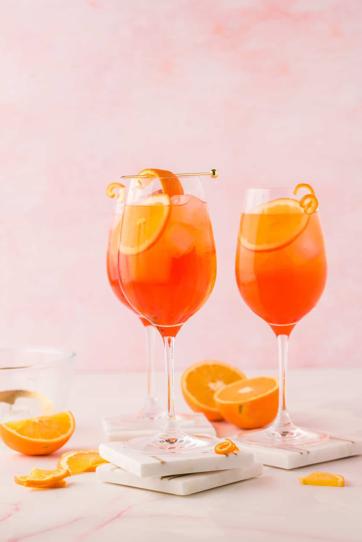 Three wine glasses filled with an orange drink and orange slices.
