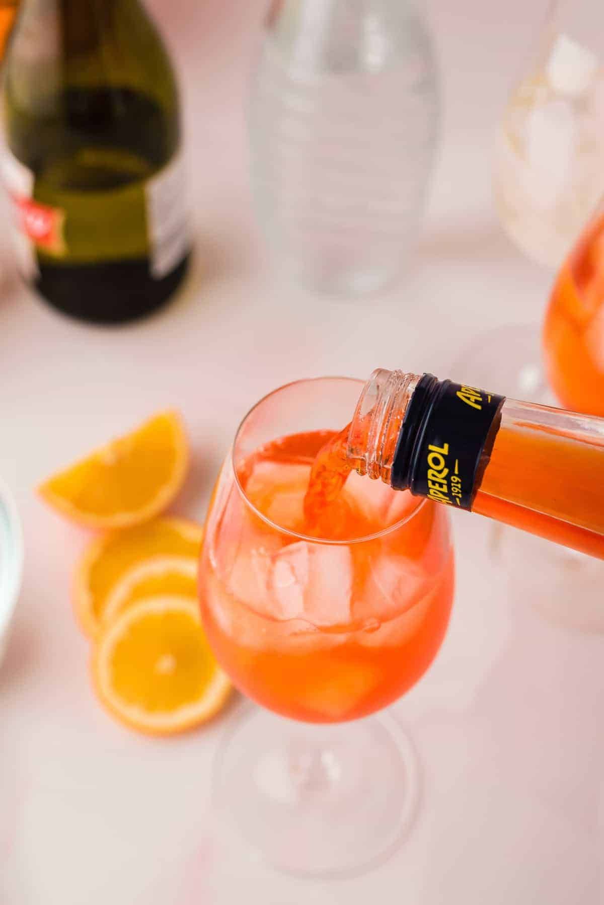 Aperol being poured into a wine glass with ice.