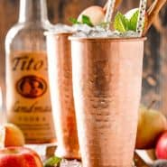 Two moscow mules in copper cups, titos vodka in the background.