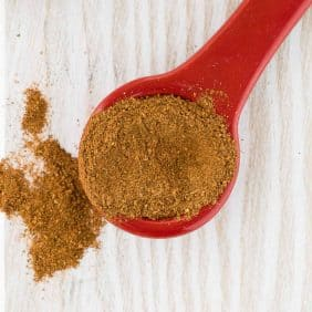 Overhead view of apple pie spice on a red ceramic measuring spoon.