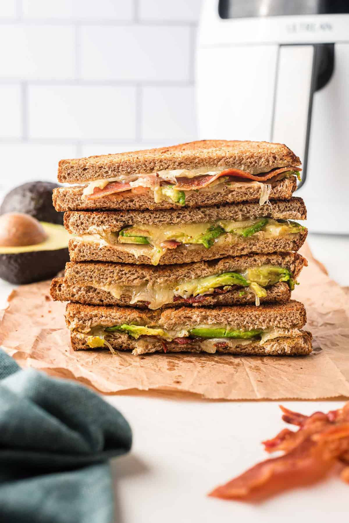 Stacked sandwich halves filled with bacon, avocado, and melted cheese.