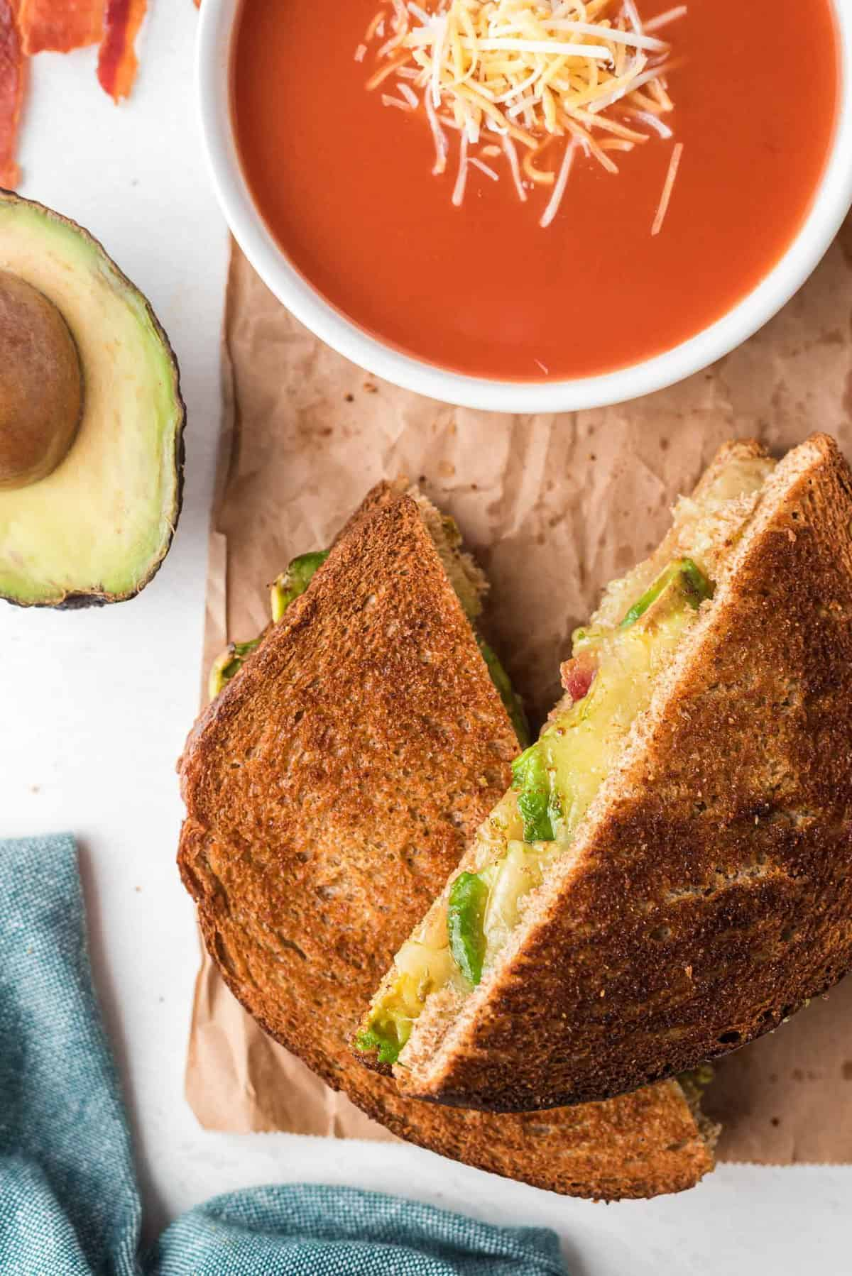 Sandwich halves that halve been toasted, filled with avocado, cheese, and bacon, served with tomato soup.