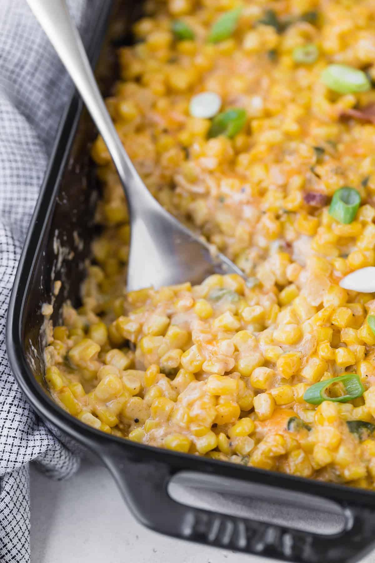 Cheesy corn casserole in a black casserole dish with a silver spoon.