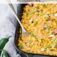 Creamy cheesy corn in a black casserole dish with a text overlay containing the recipe title.
