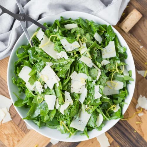 Overhead view of a white bowl with an arugula salad with parmesan and lemon on a wooden background.