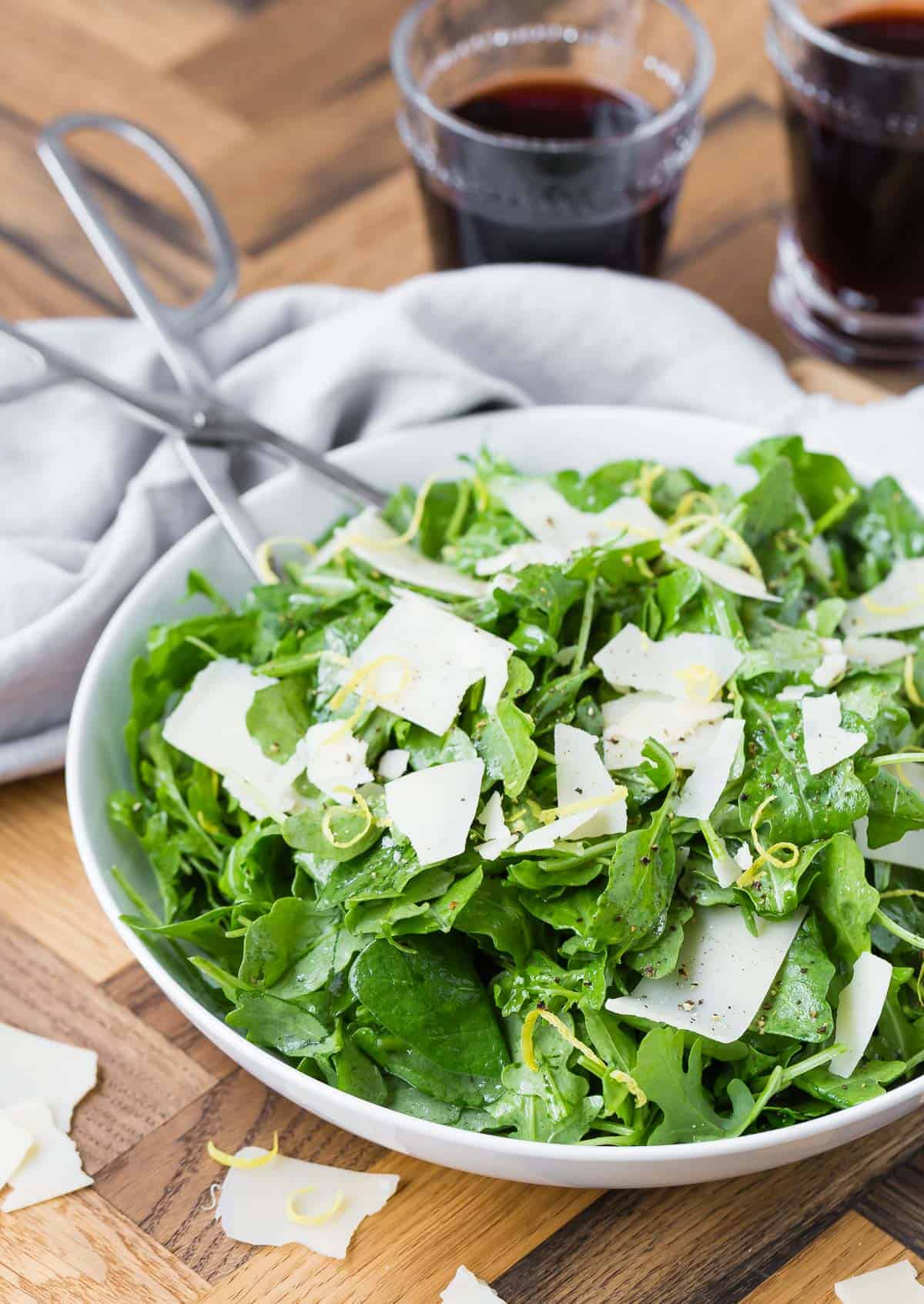A simple and classic arugula salad in a white bowl with silver tongs in it.
