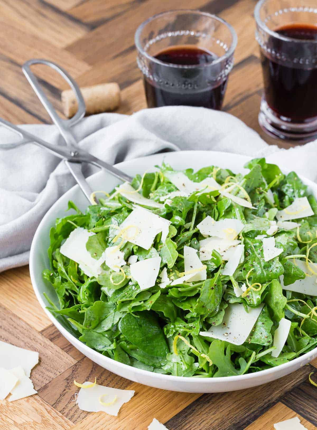 Arugula, parmesan and lemon zest in a white bowl on a wooden background, with two glasses of red wine.