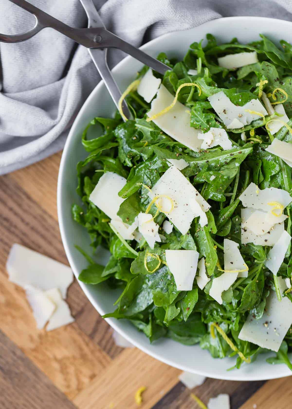 Overhead view of a salad made with arugula, parmesan, and a lemon vinaigrette.