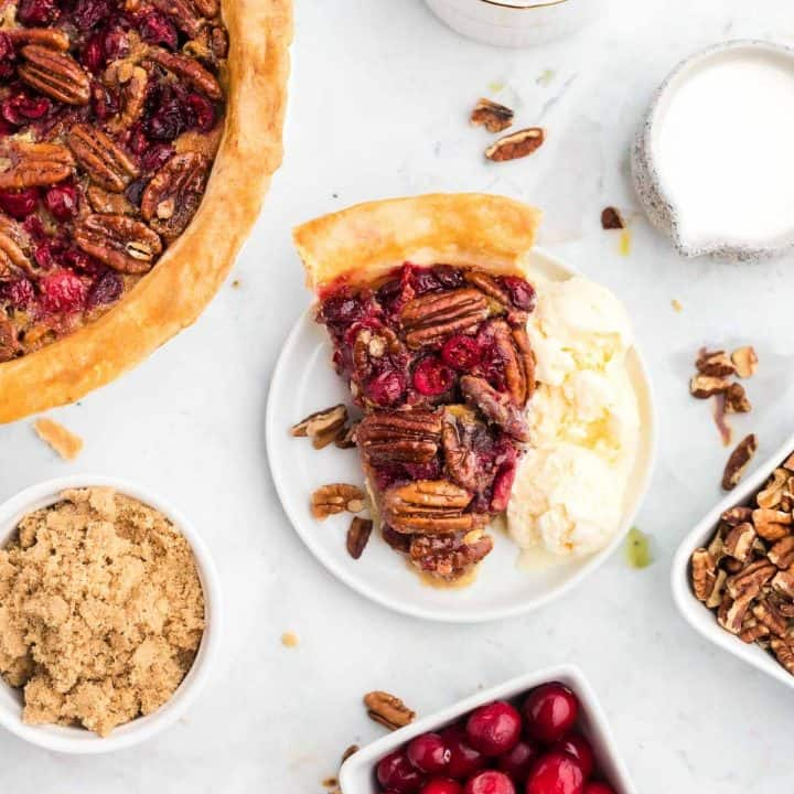 Overhead view of cranberry pecan pie on a white plate surrounded by ingredients and more pie.