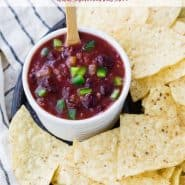 "Red salsa in a bowl, text overlay reads ""2 ingredient cranberry salsa, rachelcooks.com"""