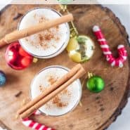 Overhead view of two glasses of egg nog, topped with cinnamon sticks.