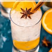 Orange and anise gin and tonic on a dark blue background.