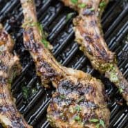 "Overhead view of lamb on a grill pan. Text overlay reads ""garlic herb grilled lamb chops, rachelcooks.com"""