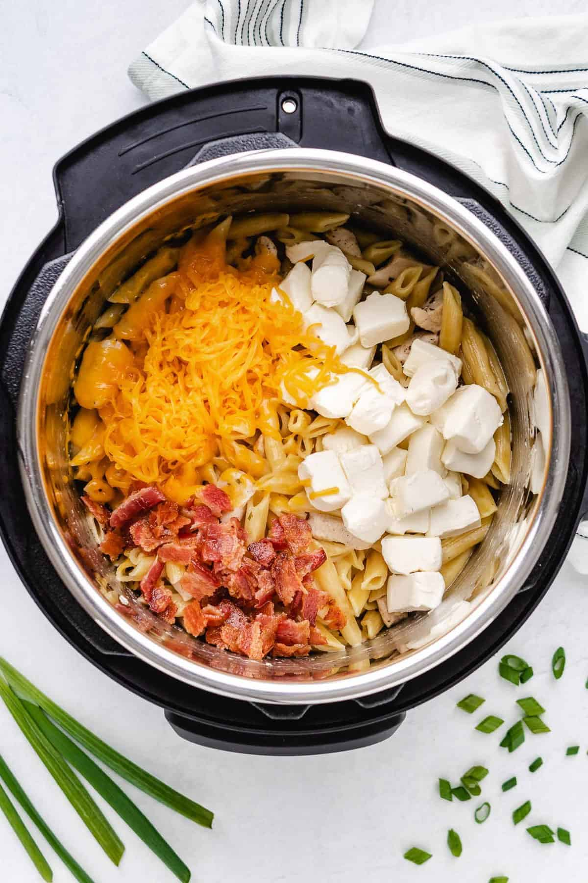 Cheddar cheese, cubed cream cheese, and cooked bacon on top of cooked pasta in an instant pot.