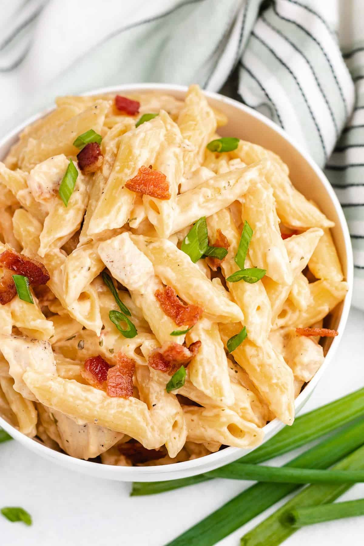 Pasta with chicken and a cream sauce, in a white bowl, garnished with green onions.