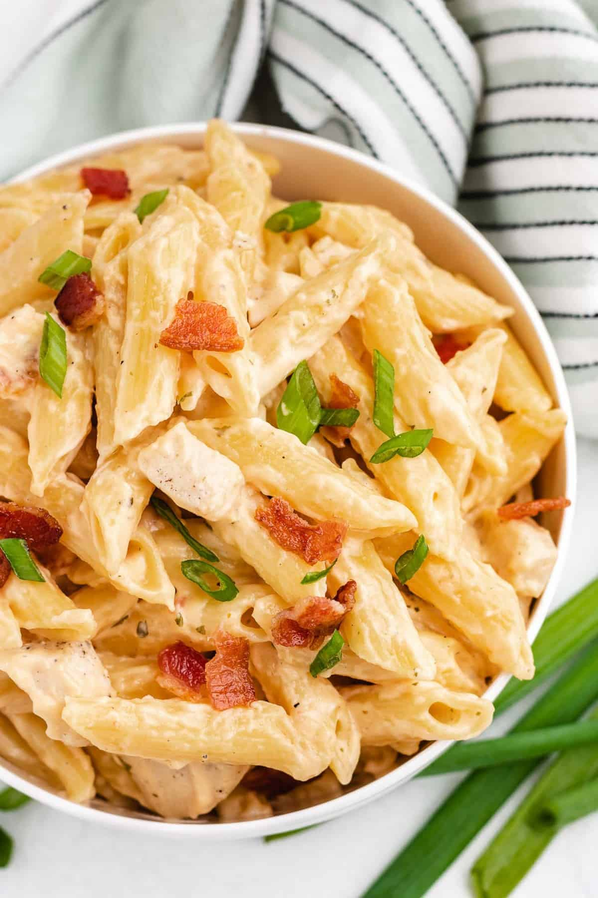Overhead view of pasta garnished with green onions and bacon.