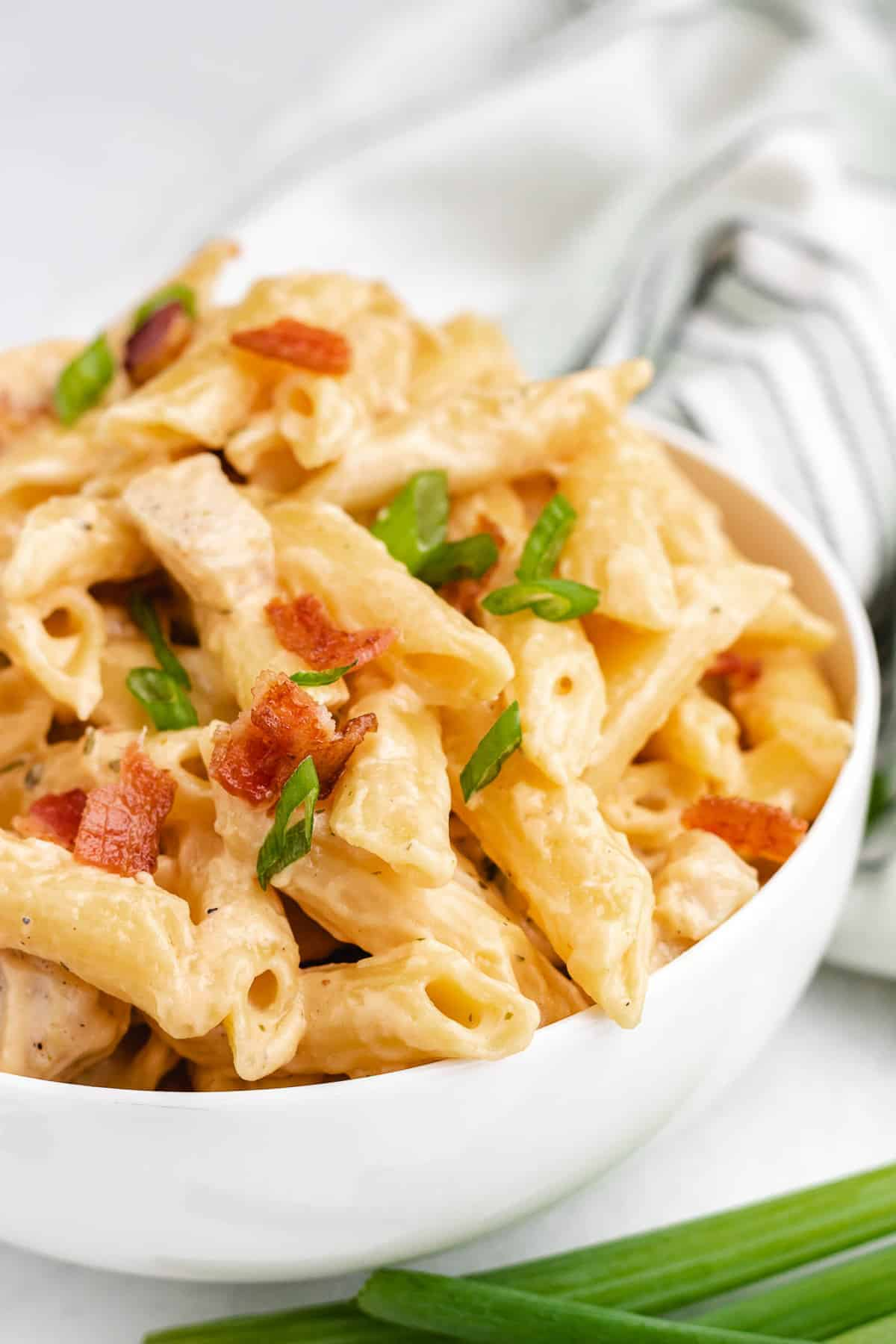 Close up of creamy pasta in a bowl, topped with green onion and bacon.