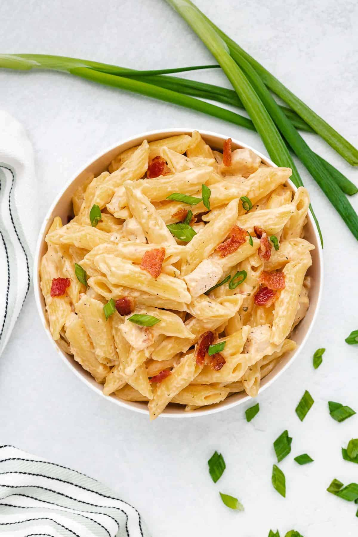 Creamy chicken pasta in a bowl with green onions and bacon.