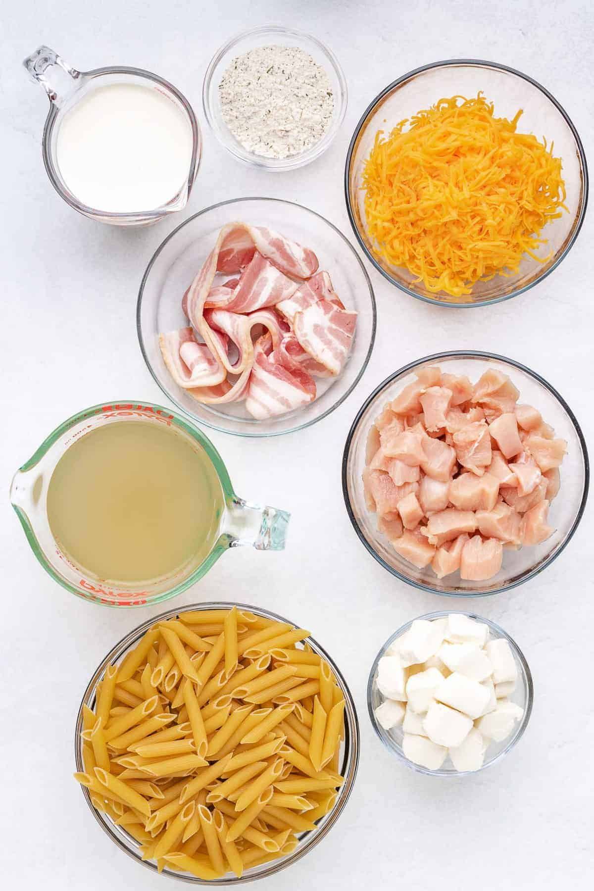 Overhead view of glass bowls of ingredients: pasta, chicken, bacon, cream cheese, cream, ranch, broth.