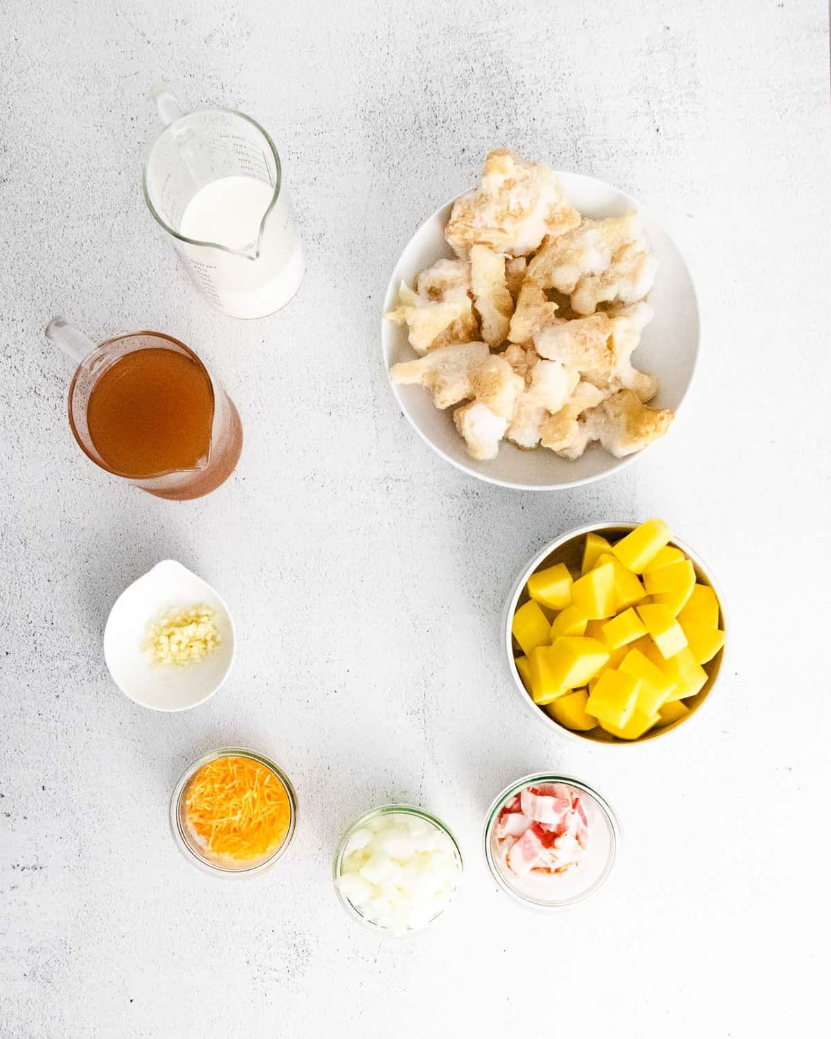 Overhead view of ingredients in bowls: potato, cauliflower, broth, milk, cheese, bacon.