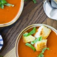 Overhead view of two bowls of tomato soup topped with croutons and fresh basil.