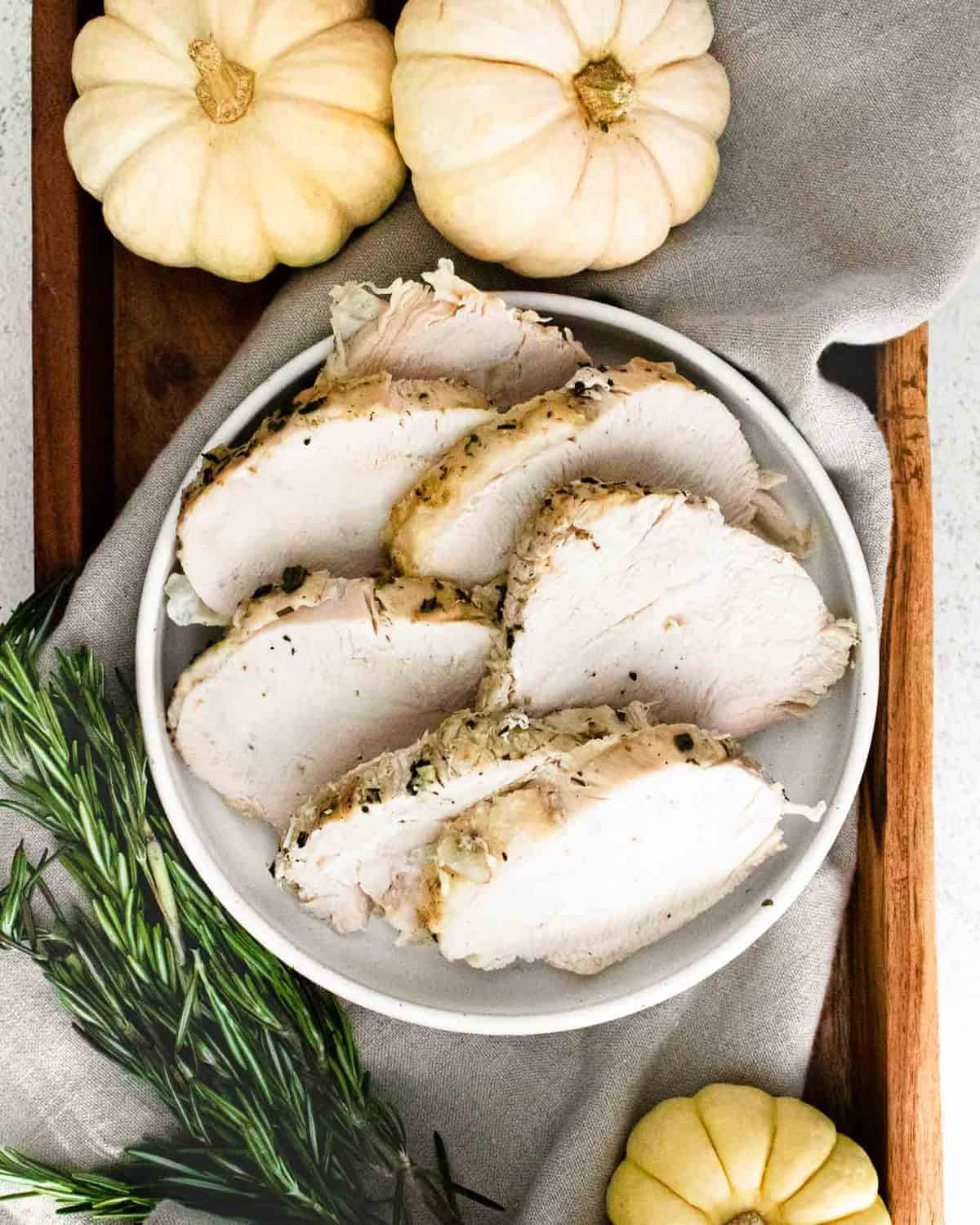Overhead view of white meat turkey sliced on a white platter.
