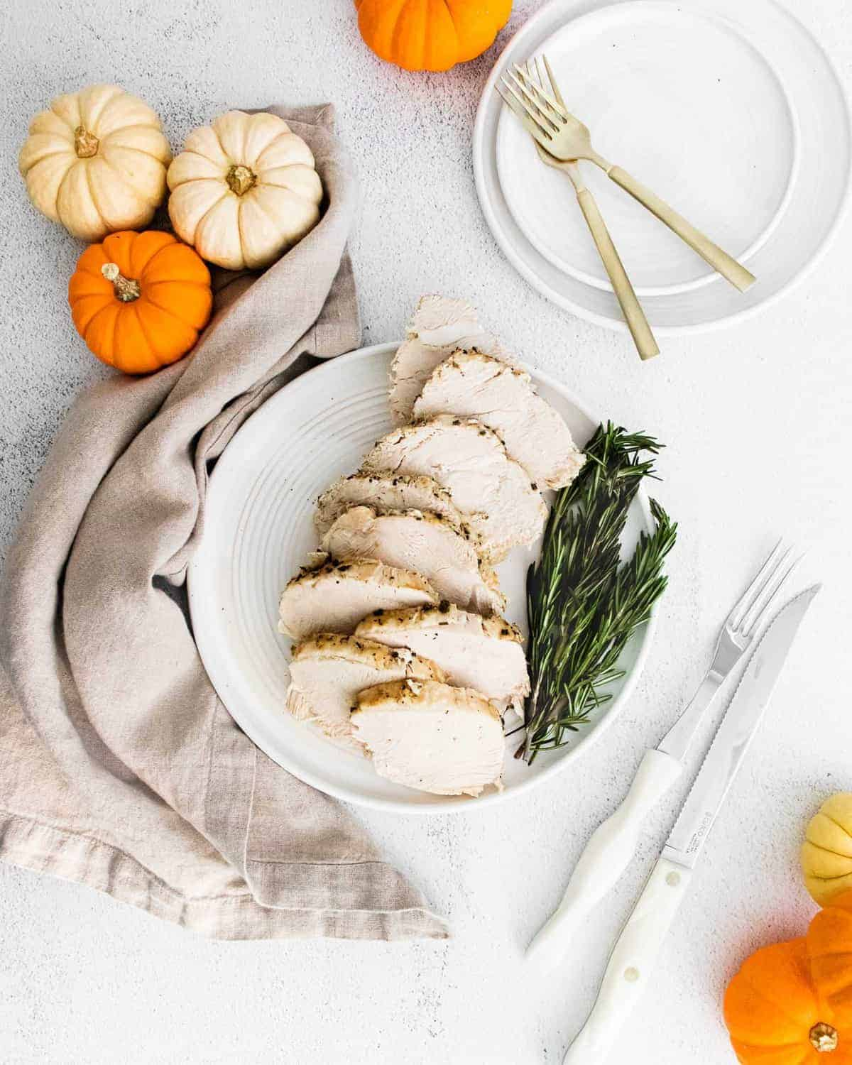 Overhead view of sliced turkey breast with rosemary sprigs and small pumpkins.
