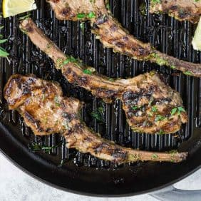 Lamb chops on a grill pan, sprinkled with fresh herbs.
