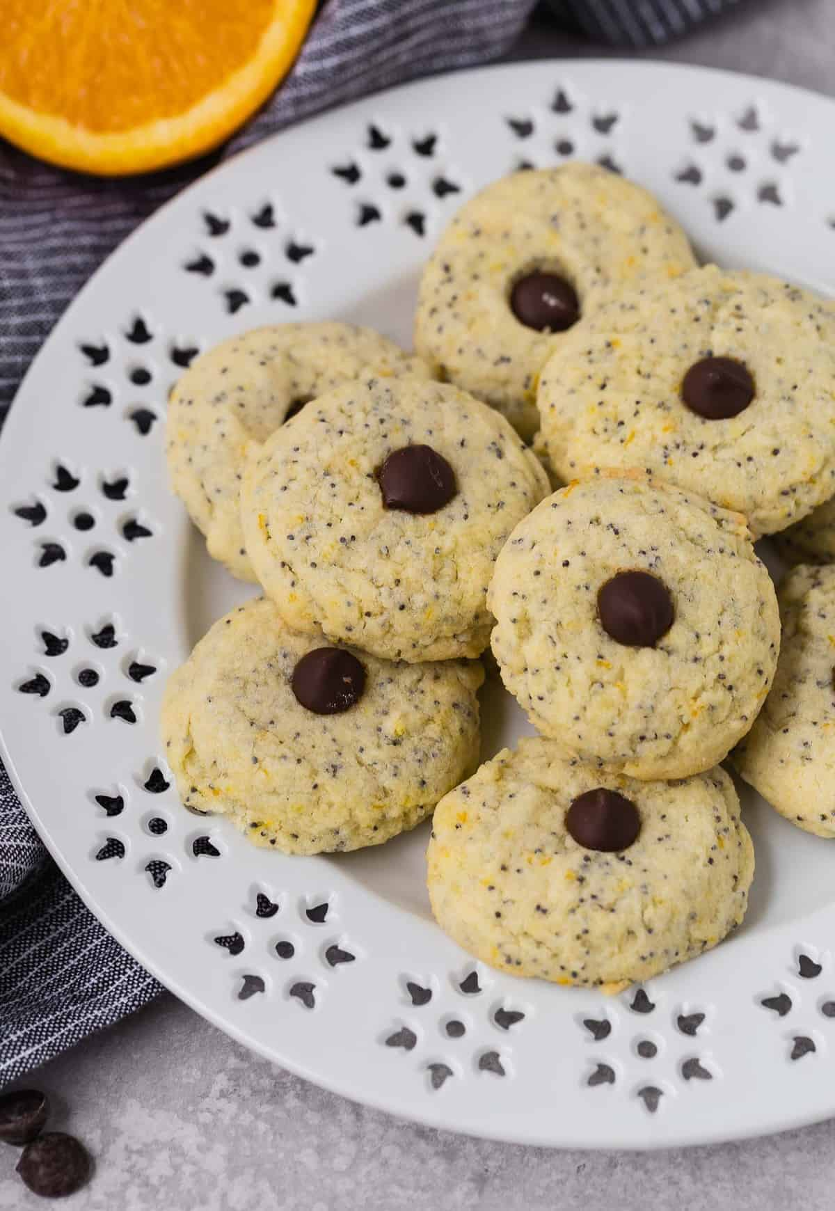 Cookies flecked with poppy seeds and orange zest on a white plate. Each cookie is topped with a chocolate chip.