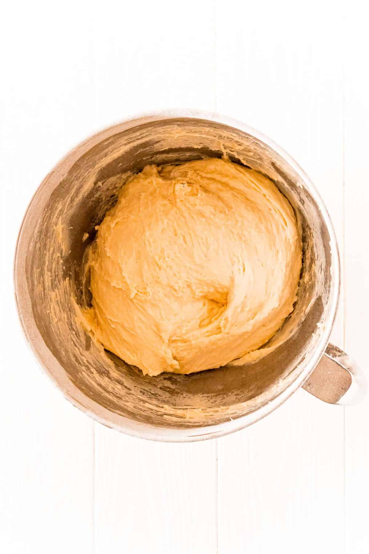Bread dough in a metal mixing bowl on a white background.