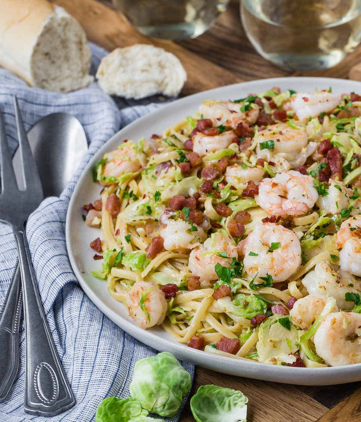 A large serving plate of pasta with brussels sprouts and shrimp. Bread and wine in background.