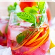 """Brightly colored red drink with pomegranate arils, citrus slices, and fresh mint. Text overlay reads """"sparkling pomegranate punch"""""""
