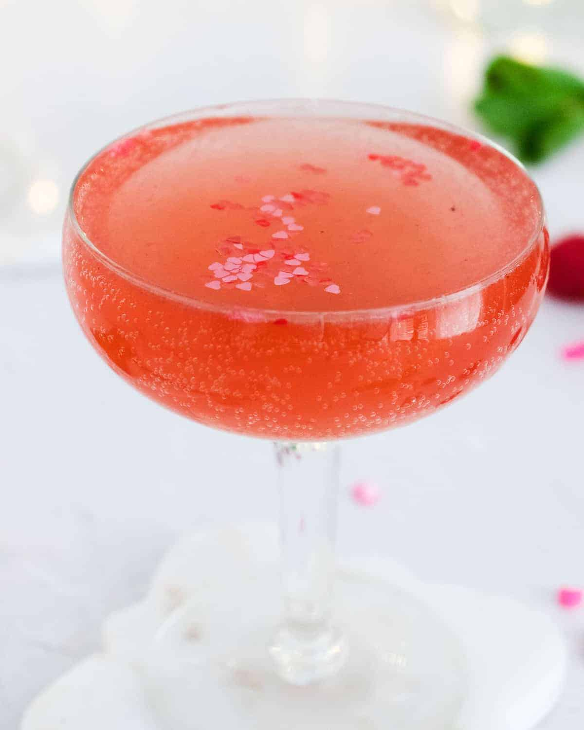 Close up of a sparkling pink drink with heart sprinkles.