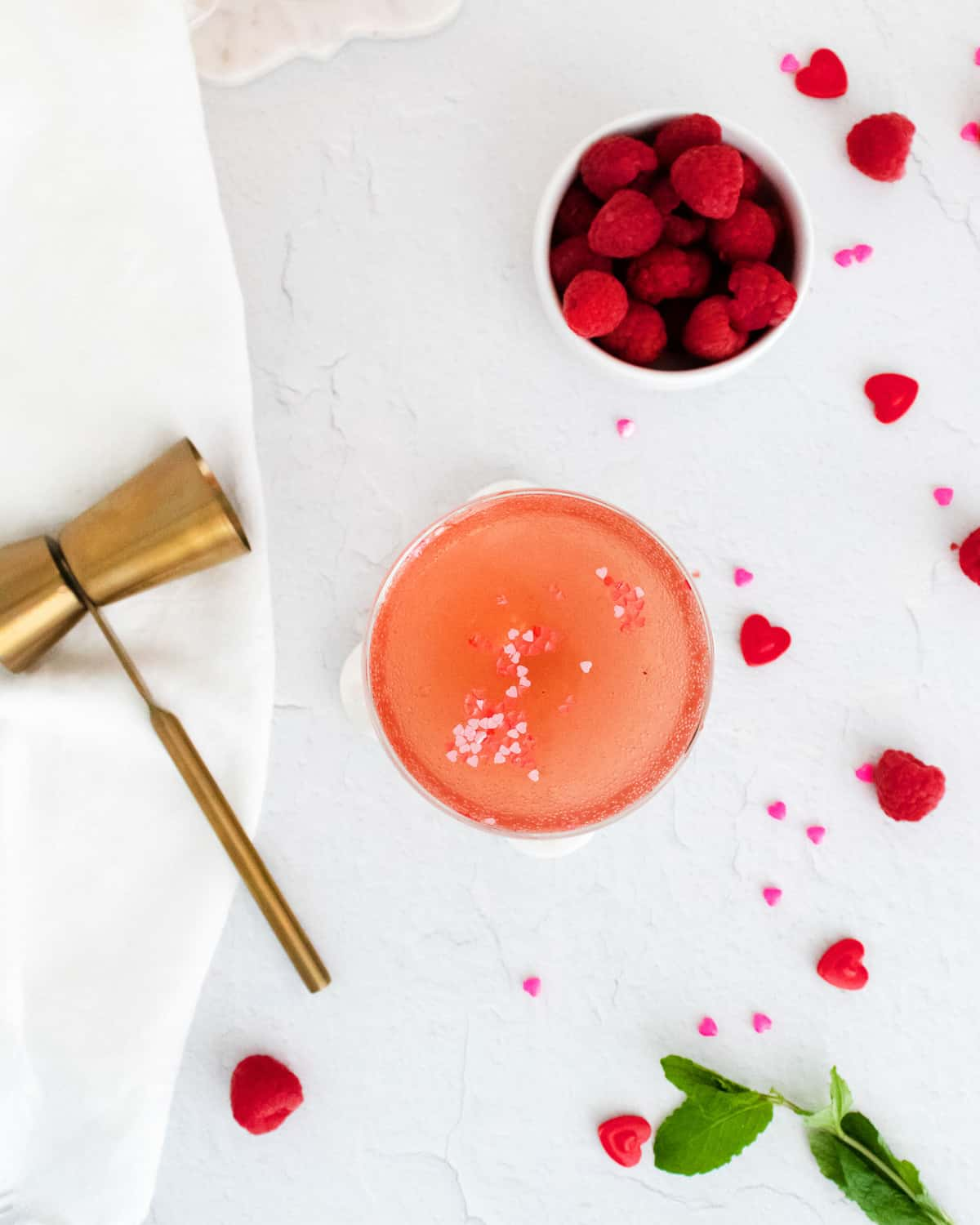 Overhead view of a light pink cocktail, raspberries scattered around.