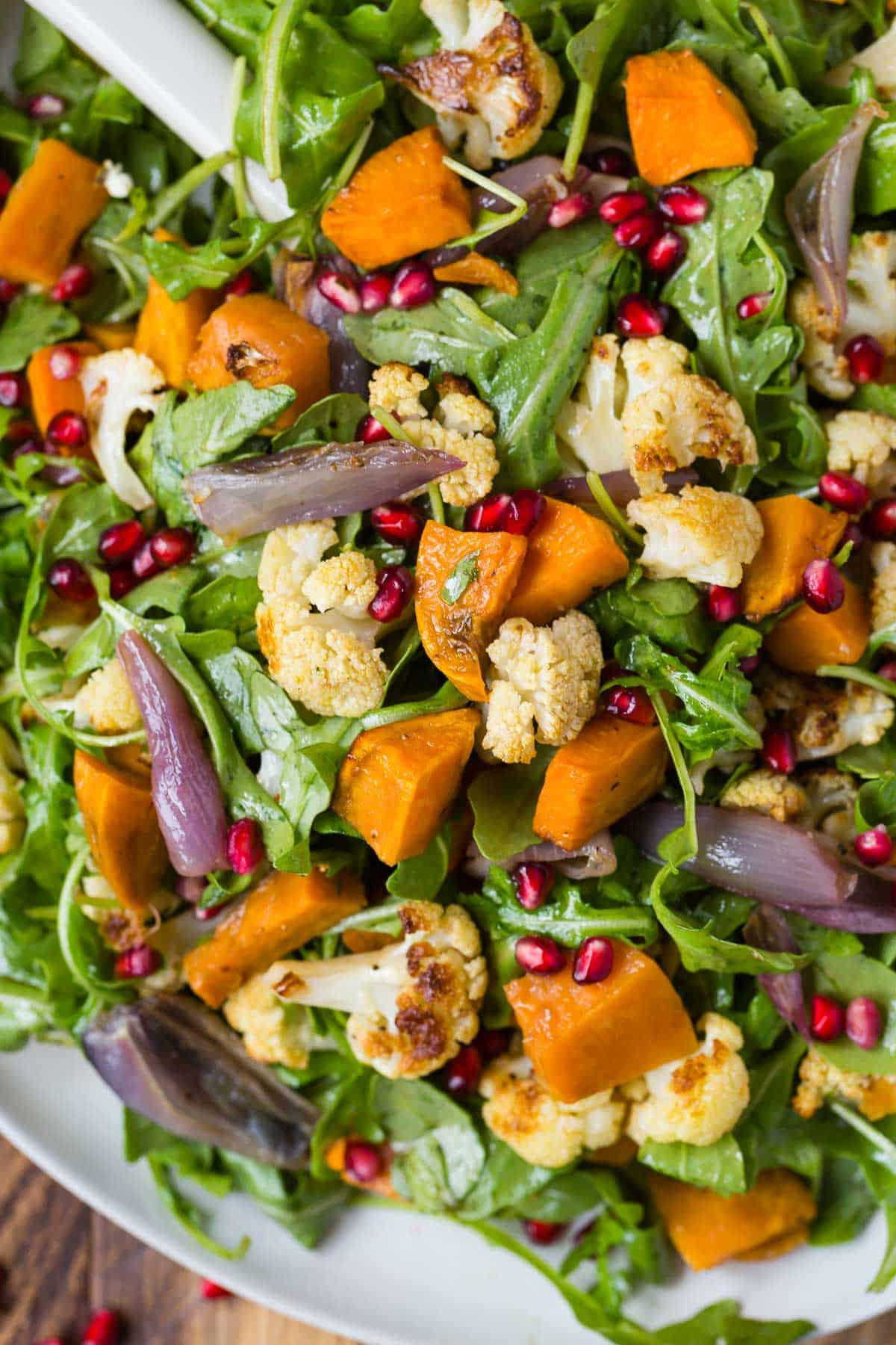 Close up of arugula salad with roasted cauliflower and sweet potatoes.