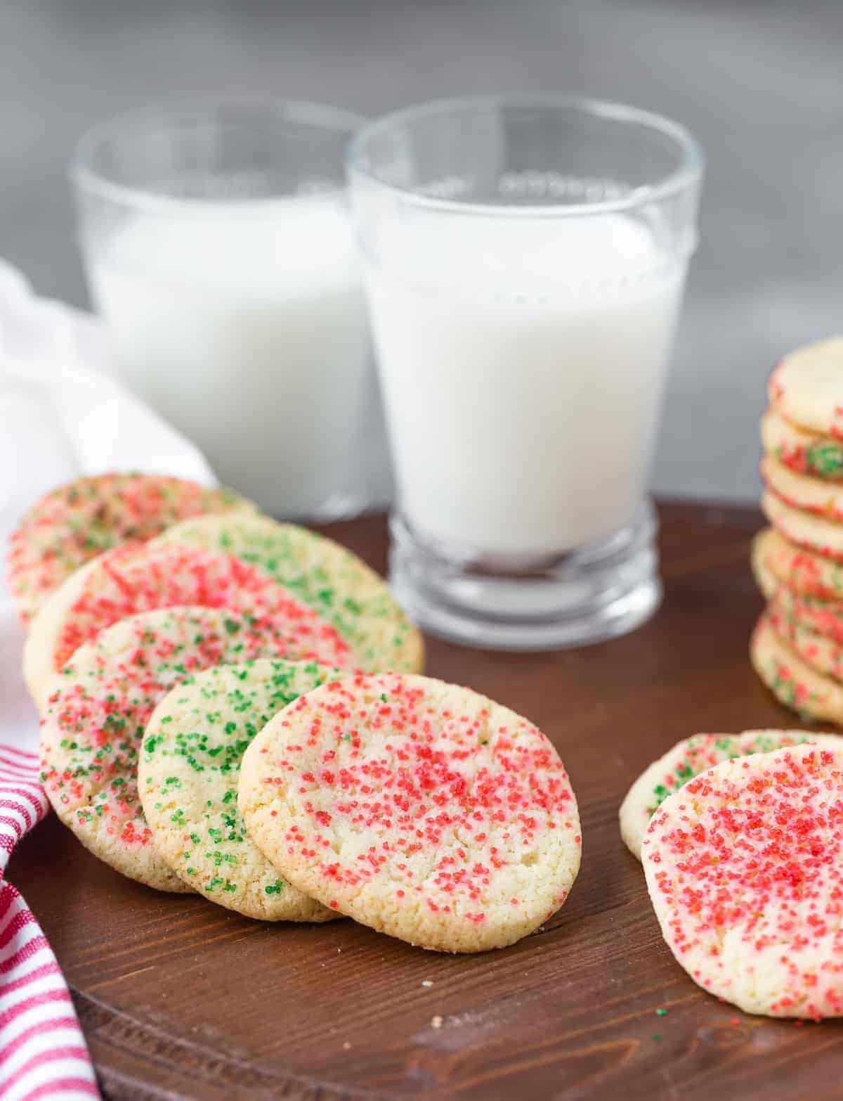 Cookies decorated with red and green sugar, milk in background.