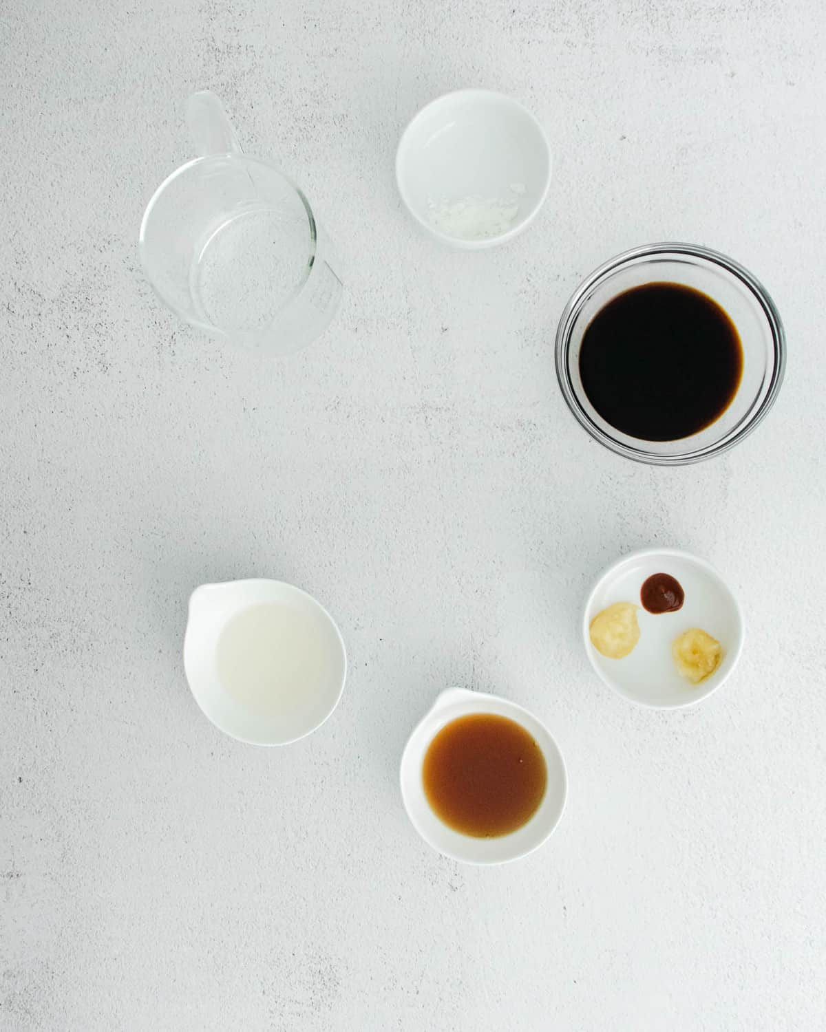 Sauce ingredients in small bowls on a light grey surface.
