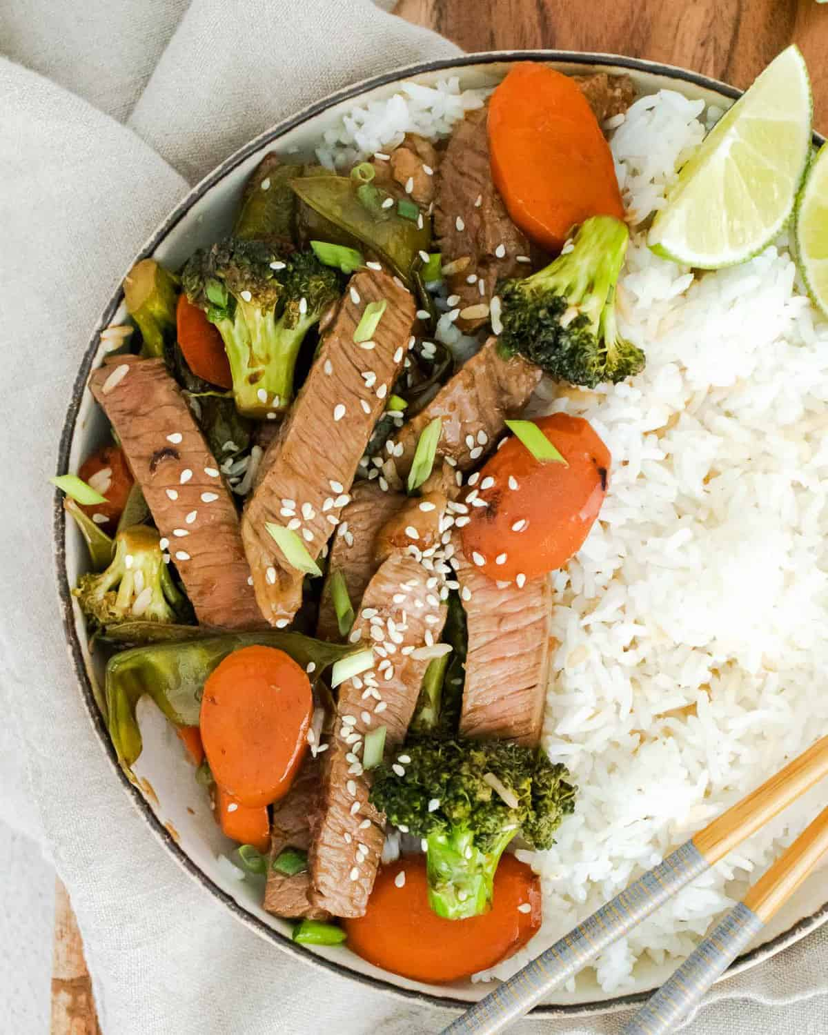 Cooked beef and vegetables in a bowl with rice, topped with sesame seeds.