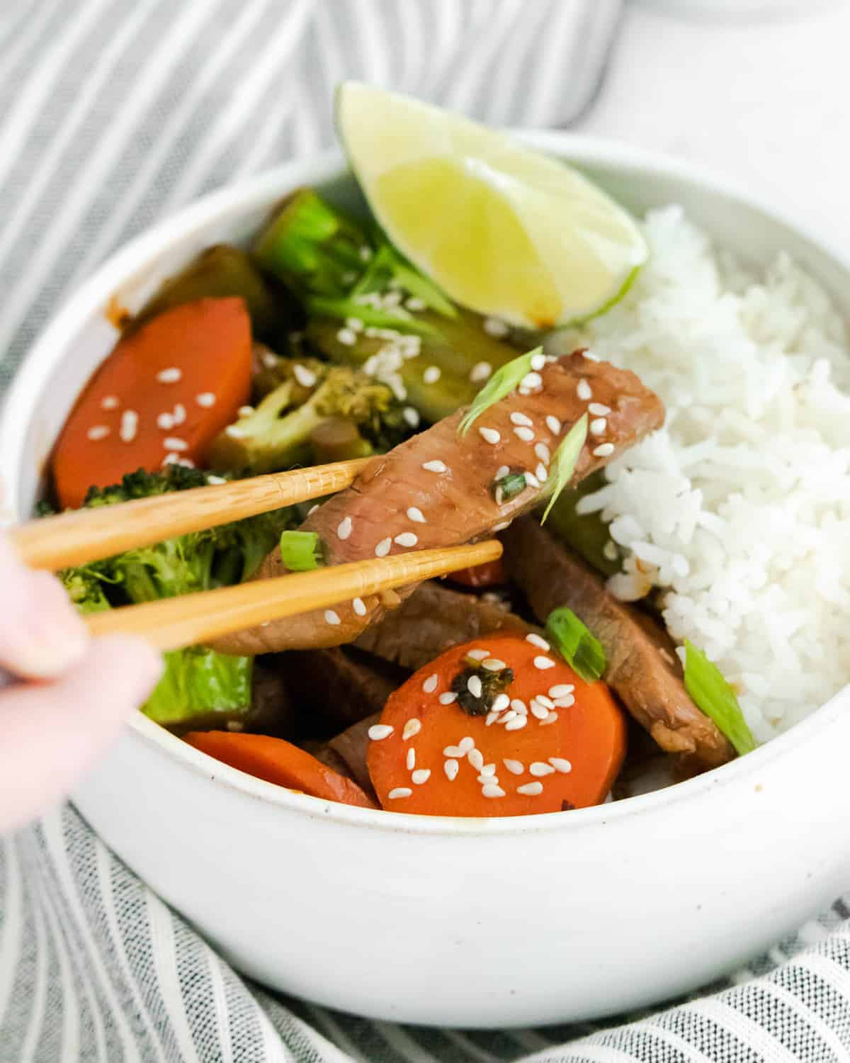Chopsticks taking a piece of cooked steak out of a bowl of rice, beef, and vegetables.