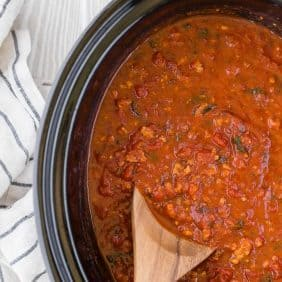 A wooden spoon inserted into a black crockpot full of spaghetti sauce.