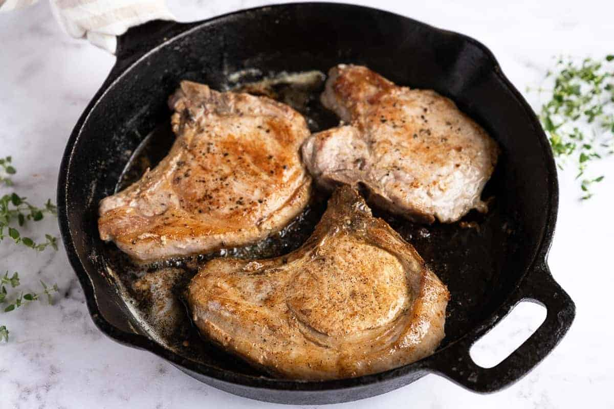 Browned pork chops in a cast iron skillet.