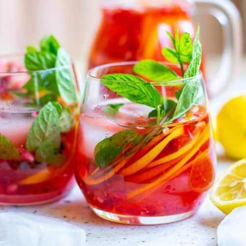 Brightly colored red drink in a stemless glass, full of citrus slices and mint leaves.