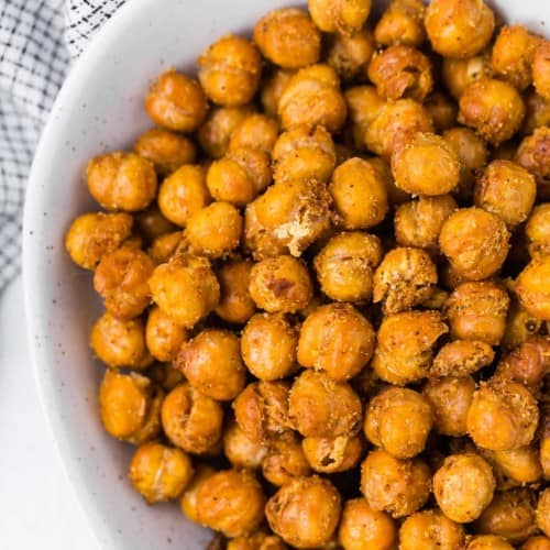 Overhead view of crispy seasoned chickpeas in a white bowl.