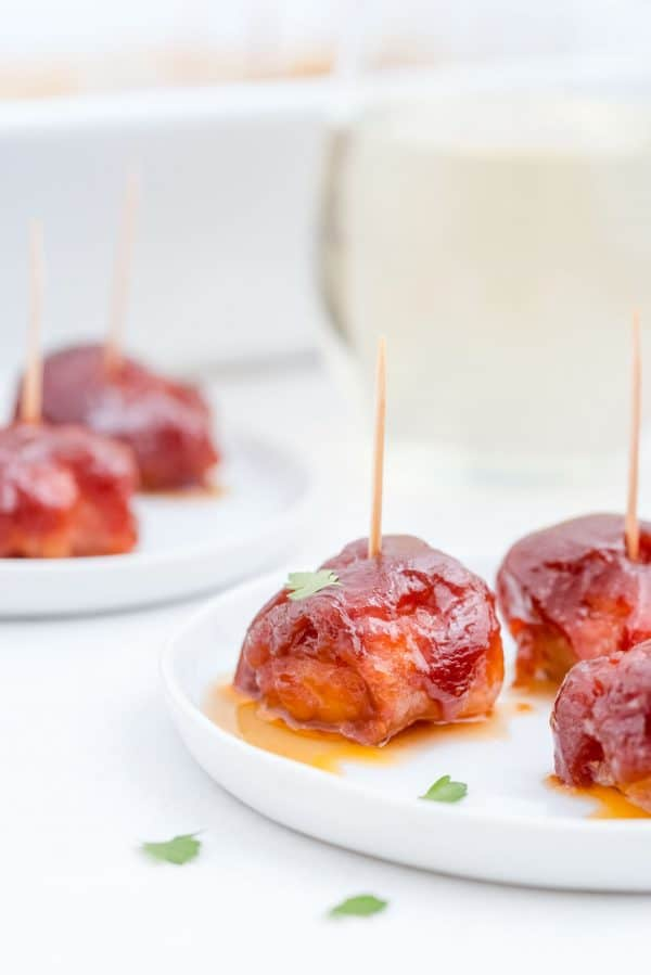 A water chestnut, wrapped with bacon, on a plate with others.