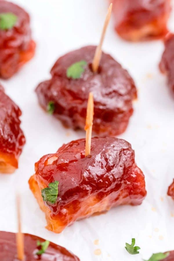 Bacon wrapped water chestnuts on a white platter.