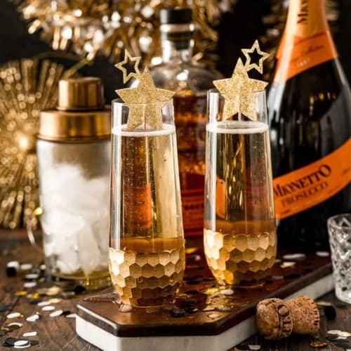 Two stemless champagne classes with a shaker, ice, bourbon, and prosecco in the background. Drinks are garnished with gold stars.