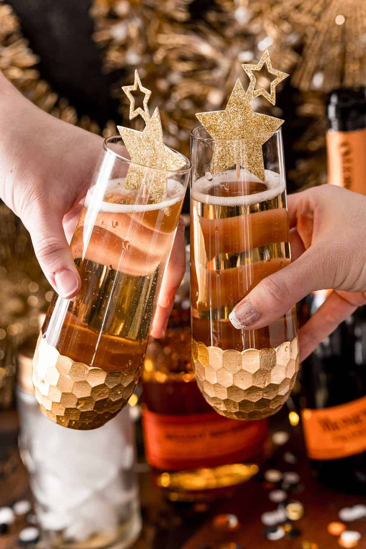 Two hands holding stemless champagne flutes filled with a light brown drink.