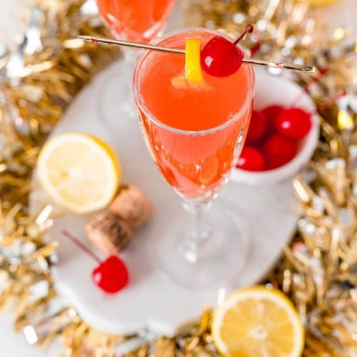 Overhead view of a light red cocktail garnished with lemon and a maraschino cherry.