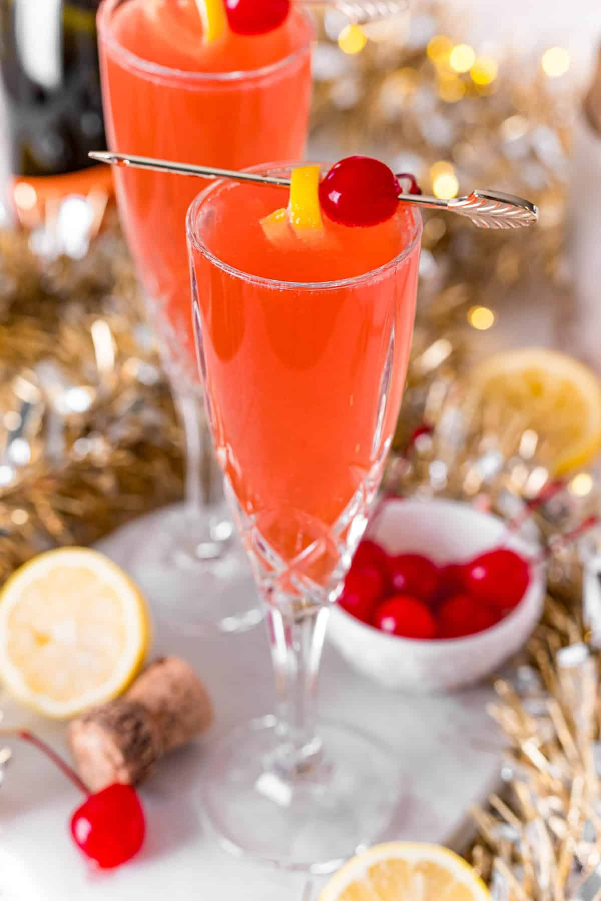 Cherry french 75 garnished with cherry and lemon peel.
