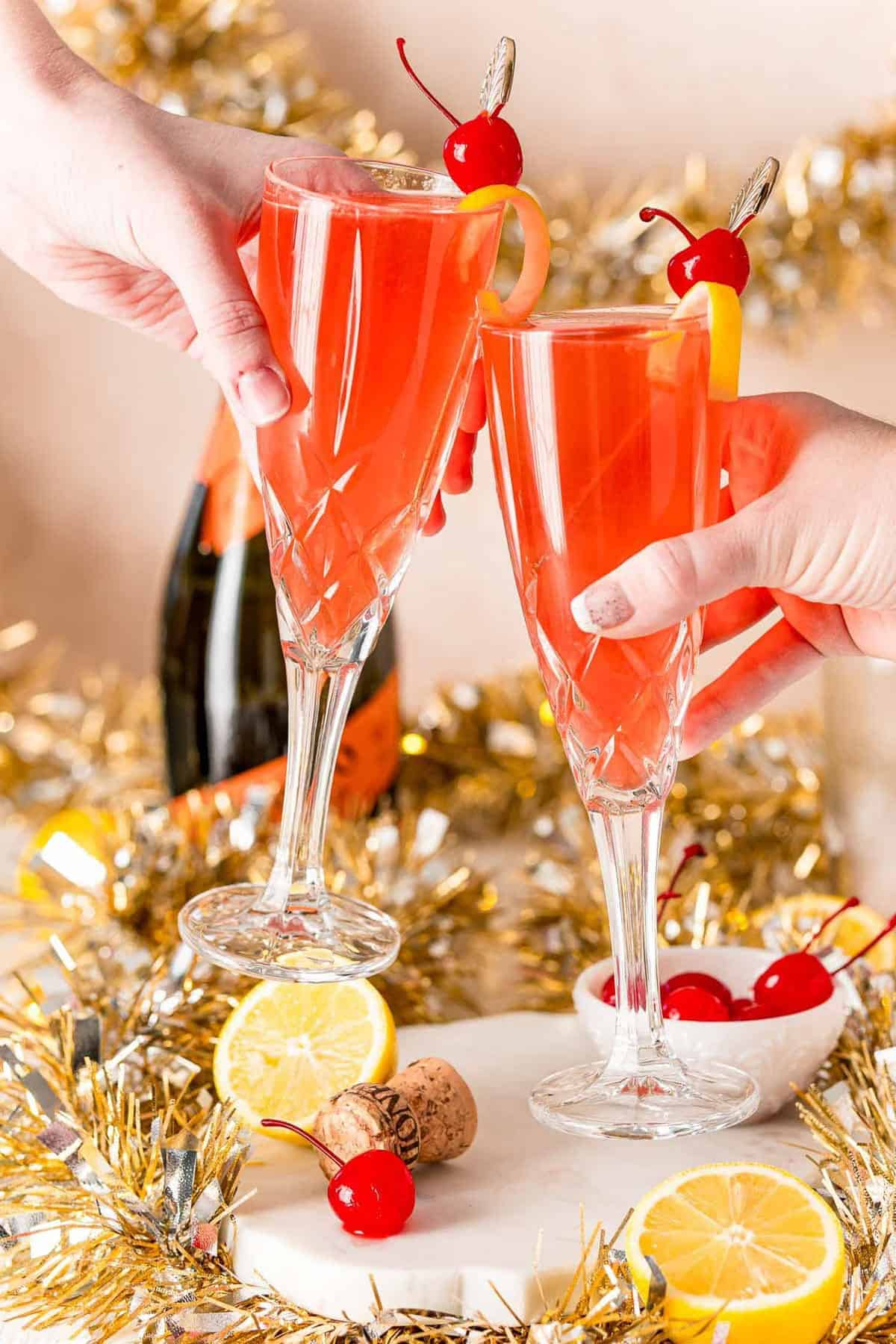 A champagne toast with light red liquid in champagne glasses.